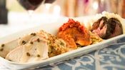 Plate of char-grilled filet of beef, sustainable fish of the day and slices of turkey breast
