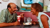 A man and a woman smiling at each other as they enjoy an ice cream sundae and a banana split