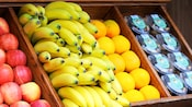 Fresh and vibrant selections of apples, bananas and oranges for sale alongside packages of trail mix