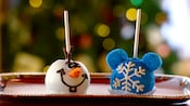 Holiday-themed cake pops on a tray, decorated like Olaf the snowman and a snowflake with Mickey ears