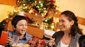 Mother and son smiling and laughing at a holiday feast, with a Christmas tree behind them