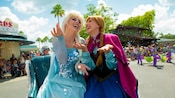 Anna and Elsa share a laugh as they ride a sleigh through Disney's Hollywood Studios