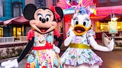 Minnie and Daisy, wearing dresses with floral patterns, pose in front of Hollywood & Vine restaurant