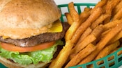 A cheeseburger with lettuce and tomatoes sits in a green plastic basket with a side of crispy fries
