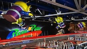 Little green men hang from the ceiling over the tables at the Pizza Planet Arcade