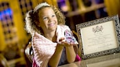 A beaming little girl wearing a tiara holds a glass slipper next to a princess proclamation