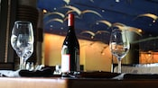 Reflections of elegance glimmering from a wine bottle and glass inside a classy dining space