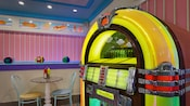 A colorful jukebox next to a café table with 2 chairs in Beaches & Cream Soda Shop at Disney's Beach Club Resort