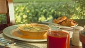 A Dungeness crab frittata, pastries and tomato juice on a table by a window