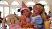 A little girl in a pink Princess Minnie outfit meets Alice at the Supercalifragilistic Breakfast