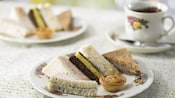 Assorted finger sandwiches with black tea on floral English tea service china