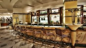 Curved bar with 8 wicker chair-stools on a tiled floor with circular designs