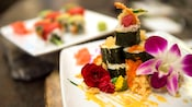 An appetizing plate of maki sushi is artfully decorated with salmon roe and exotic flowers