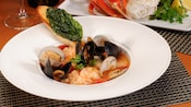 A simmering bowl of Cioppino served with clams, mussels, assorted seafood and a cilantro garnish