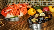 King crab legs and mussels on display in stainless steel cookware at the Friday Seafood Buffet