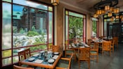 Tables set for dinner line a wall featuring 3 large windows with views of Silver Creek Falls