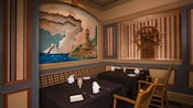 Banquette tables in a corner with a lighthouse mural and wooden ship wheel