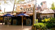 Entrance to a quick service restaurant, with 2 patio umbrellas and a sign on netting that reads 'Typhoon Tilly's, Food and Spirits'