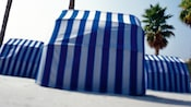 3 blue and white-striped cabanas viewed from the back