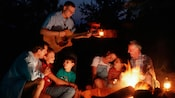 Guests enjoying a guitar player around a campfire at Disney's Fort Wilderness Resort
