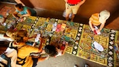 Overhead view of kids coloring in designs at a crafts table