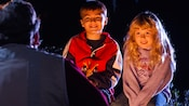Boy and girl listen with rapt attention as their faces are lit by the glow of the fire