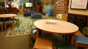 A Western-themed play room with 2 round tables and stools across from a TV-viewing area