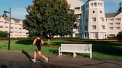 A woman runs along a wooden boardwalk on the grounds of Disney's Yacht Club Resort