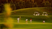 Golfer putts as 3 of his golfing group watch with their golf carts nearby