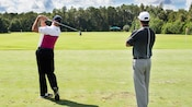 A golf instructor monitoring a Guest's swing during a coaching session at Walt Disney World Resort