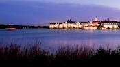 View from across the lake of Disney's Grand Floridian Resort & Spa at sunset