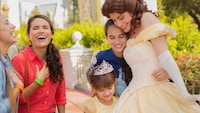 Belle outside her castle gives a heartwarming hug to 2 young girls, while their mothers look on