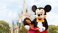 Uma garota rindo e caminhando abraçada com o Mickey perto do Castelo da Cinderela