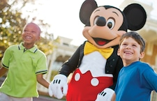 Two young boys hold hands with Mickey Mouse