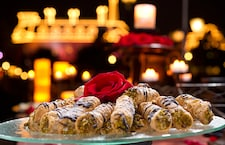 A tray of cannolis, topped with a red rose