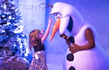 A little girl meets Olaf, the snowman from 'Frozen'