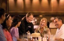 A waitress places a cake on a table in front of several smiling diners