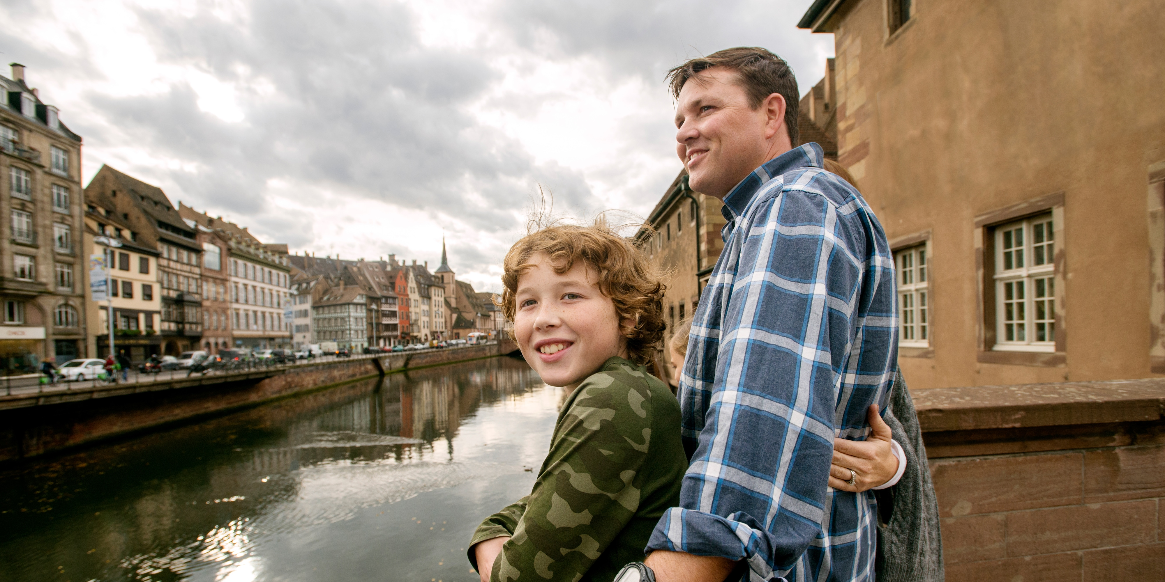 A family of 3 on a boardwalk overlooking a waterway in an old European town