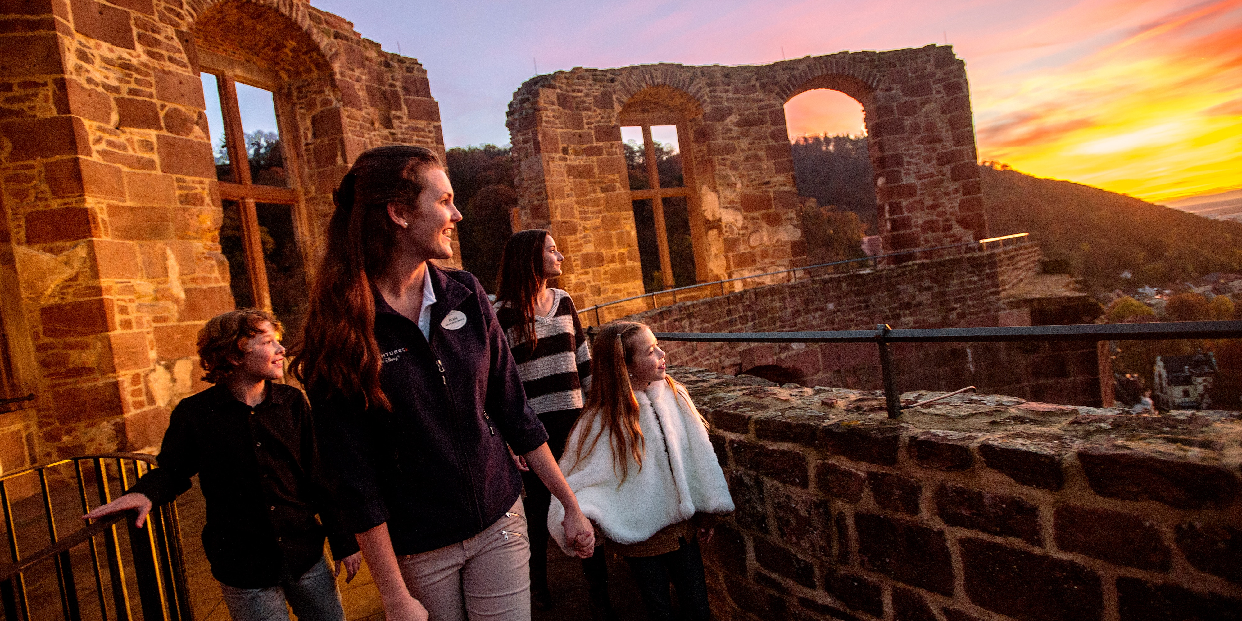 A mother with her 2 daughters and son walk outside at  Heidelberg Castle