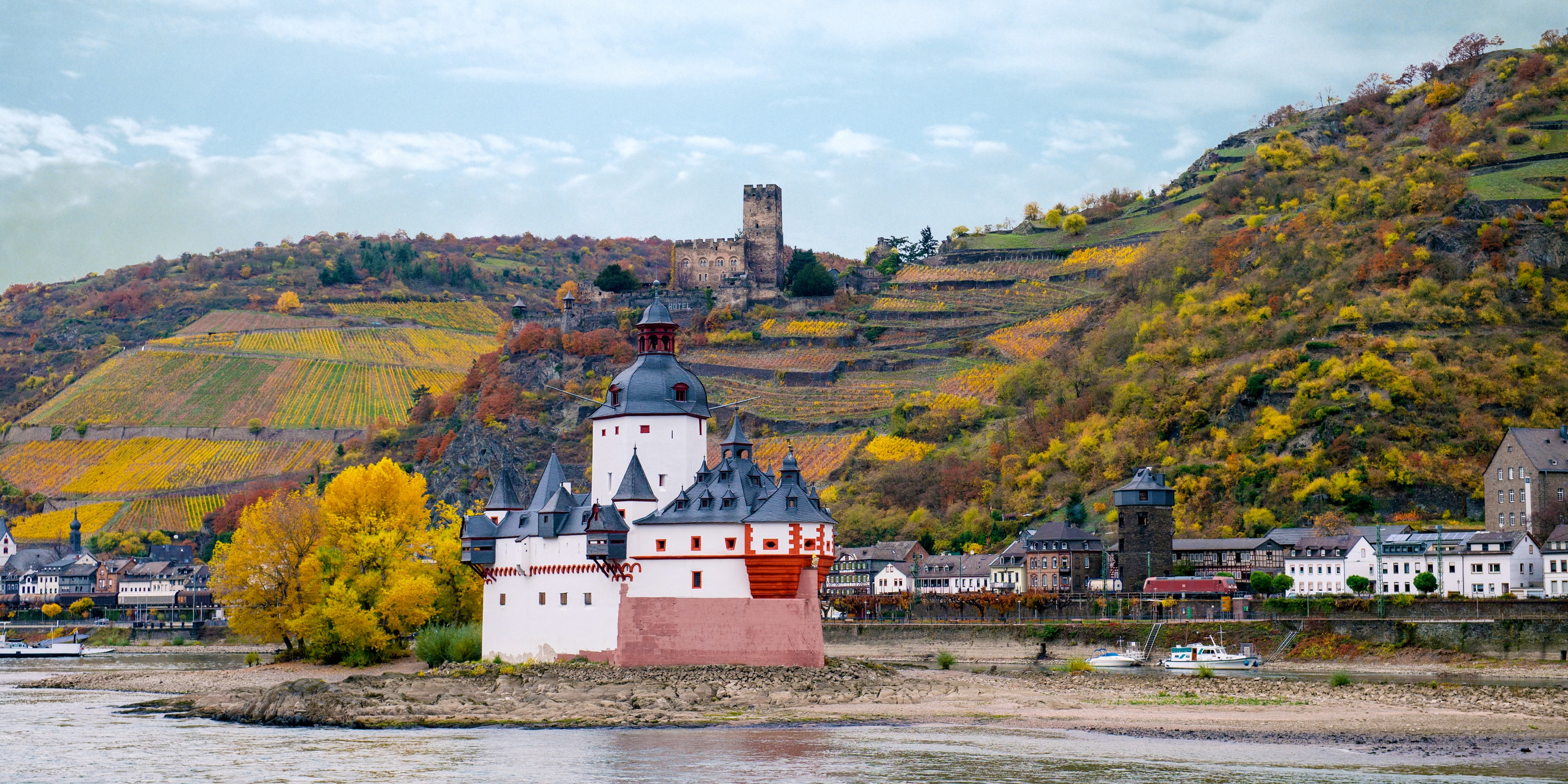 A castle on a hill and another castle near a river, with the buildings of a town lining its shore