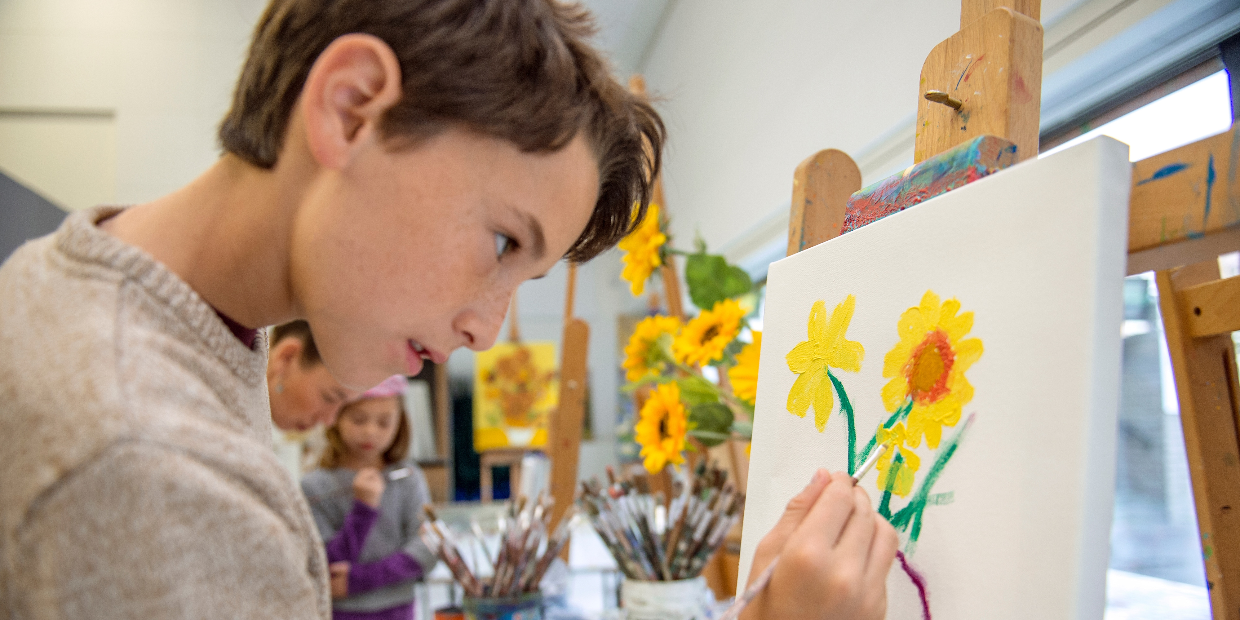 A boy stands at an easel creating a painting of sunflowers, copying the sunflowers in a nearby vase