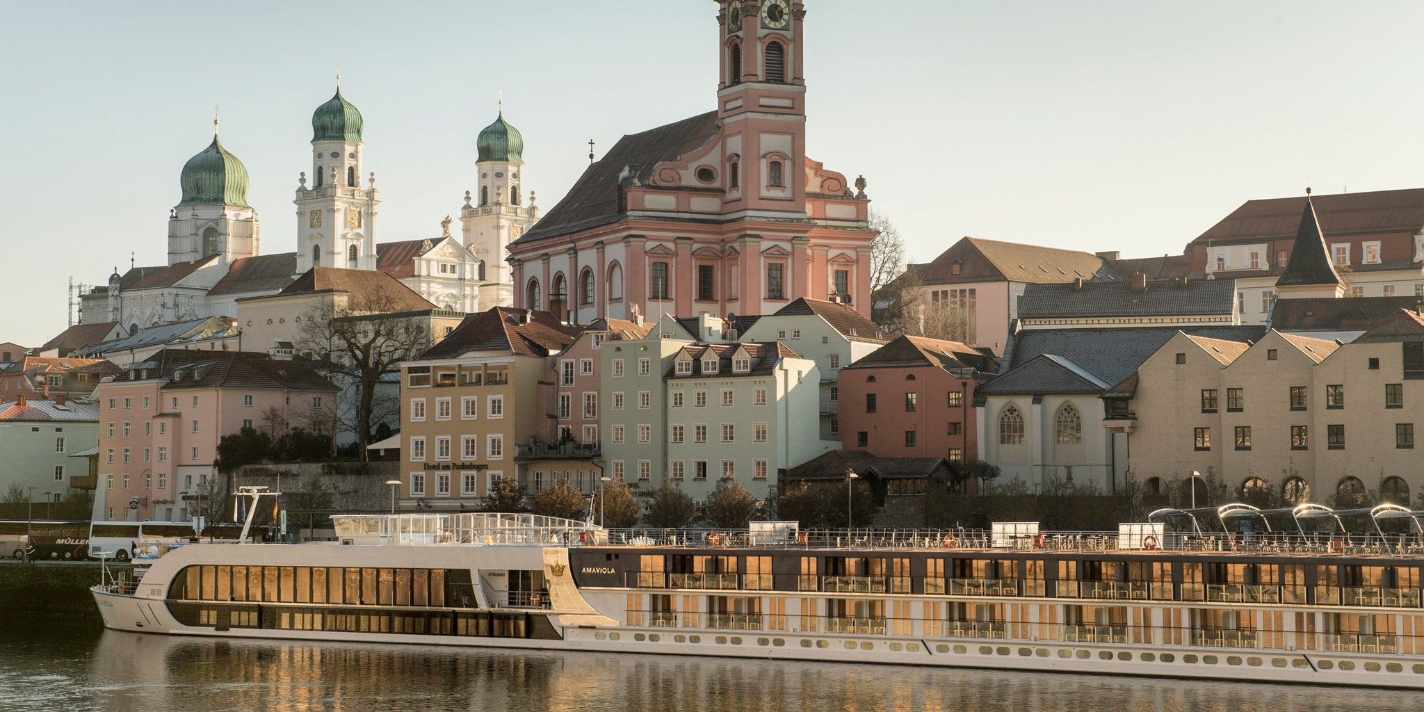 An AmaWaterways ship cruises along the Danube River past the town of Passau, Germany