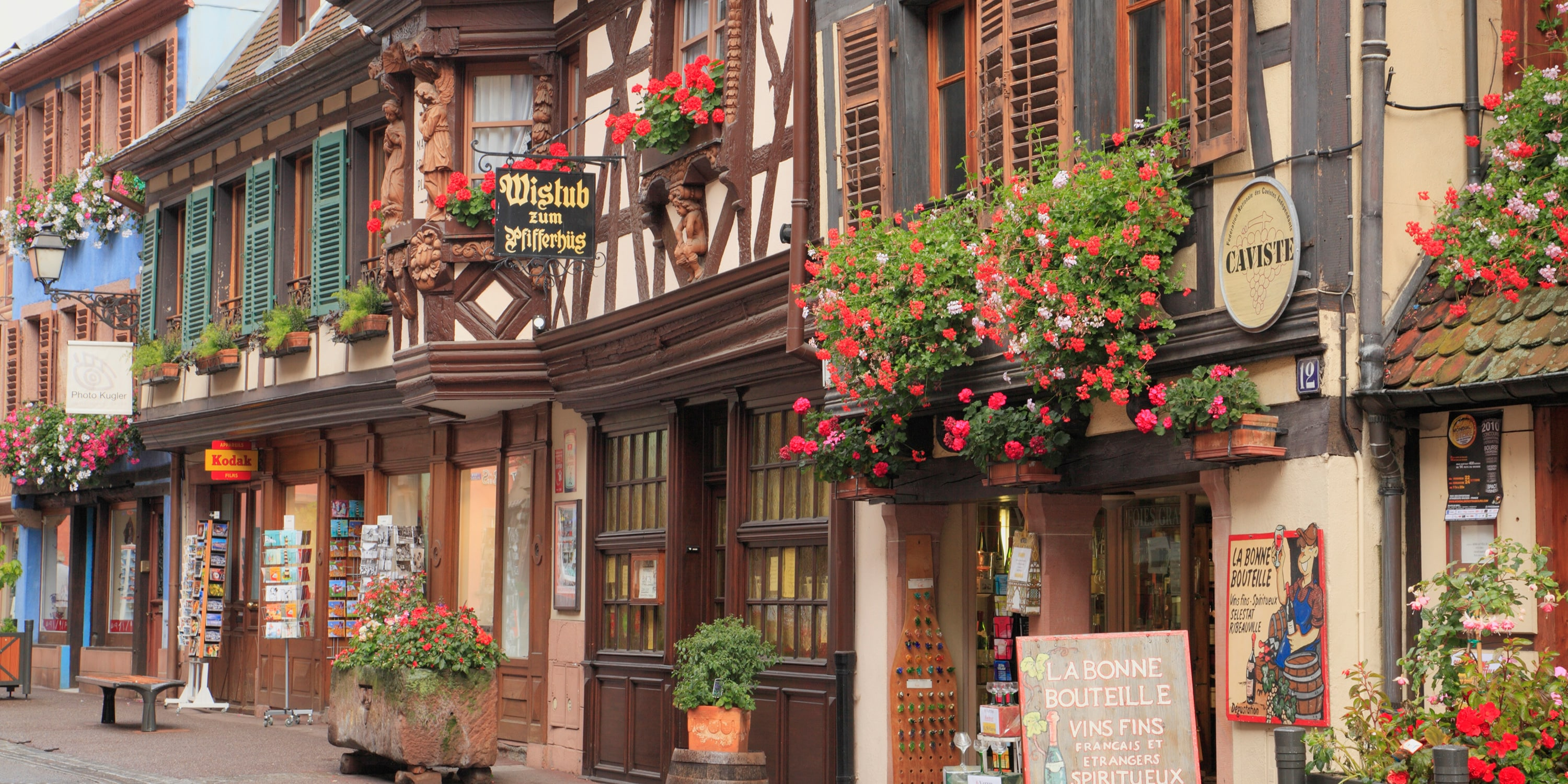 Several storefronts in traditional French style, with flowers in window boxes, line a quaint street in Riquewihr, France