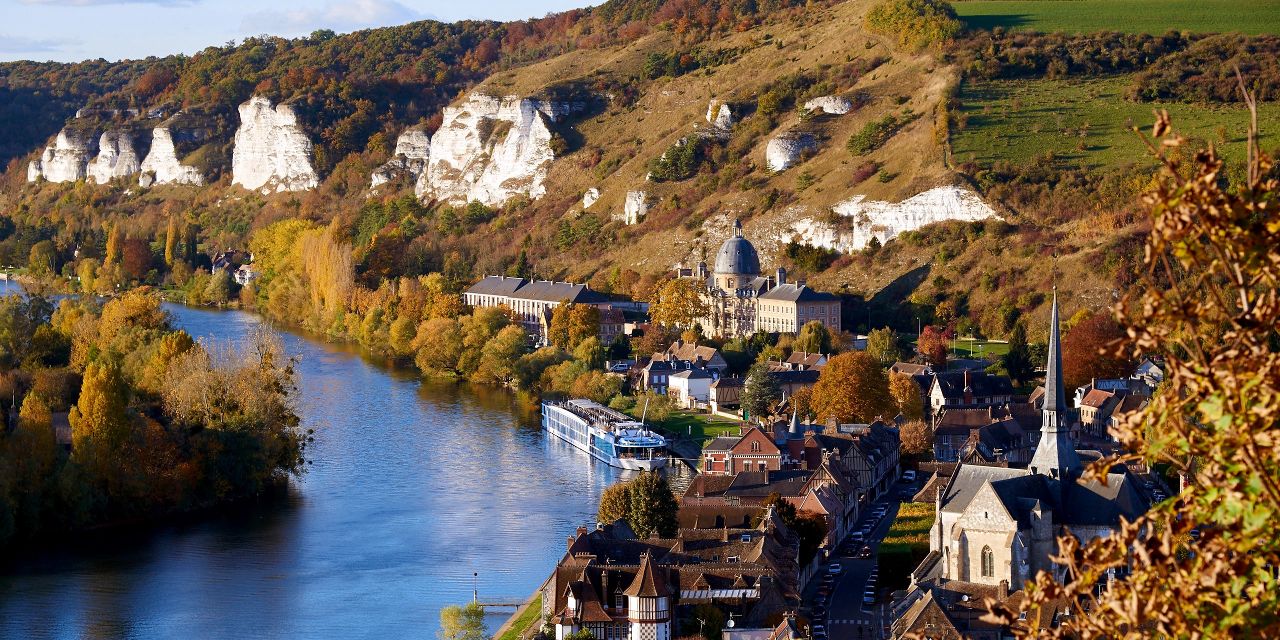 White cliffs line the hillside of Rouen, France along the Seine River