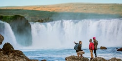 3 people stand on the rocks admiring Goðafoss Waterfall