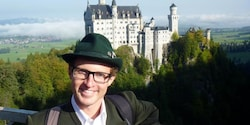 An Adventure Guide poses on a mountain near Neuschwanstein castle