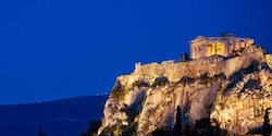 The Parthenon on top of a rocky mountain at night