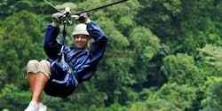 A woman zip lines above the forest