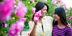 A mother and daughter stand by flowering camellia trees and share a moment of laughter