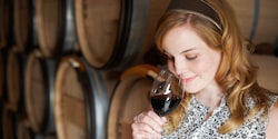 A woman stands near wine barrels and sniffs a glass of wine